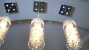 Luxueuze moderne kristalkroonluchter op een plafond op verscheidene niveaus stock footage