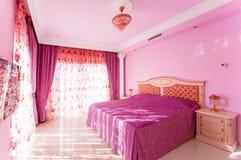 Luxueuze slaapkamer met een heldere roze kleur, met grote vensters stock afbeelding