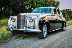 Luxuoso, bicolor, limusina do vintage em uma estrada rural de Texas Imagem de Stock