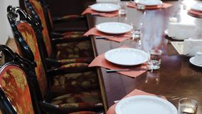 Luxuriöse Möbel: weiche Stühle mit roter Gewebepolsterung, großer Polierspeisetisch, Geschirr - in einem prestigevollen stock video