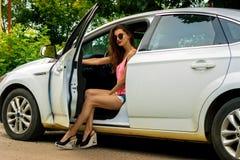 Luxuriöse Dame, die mit der Tür offen im weißen Auto sitzt Stockfotografie