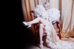 Luxuriöse Frau, die auf Stuhl, Mädchen im weißen langen Kleid sitzt Anhebendes Bein, anziehender Blick in Kamera, Dunkelheit zu Stockfotografie