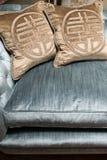 Luxuriöse Goldkissen auf teurem blauem Sofa Stockbild