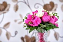 Luxuriöser rosa, roter und weißer Pfingstrosenblumenstrauß mit den Blattknospen im Kristallvase Stockfotografie