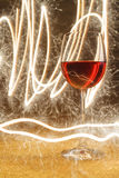 Luxuriöser Schuss des Glases des rosafarbenen Weins auf Goldfunkeln Stockbild
