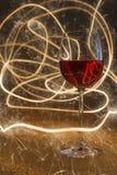 Luxuriöser Schuss des Glases des rosafarbenen Weins auf Goldfunkeln Lizenzfreies Stockbild