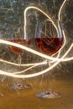 Luxuriöser Schuss von Gläsern des rosafarbenen Weins auf Goldfunkeln Stockbild