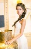 Luxuriöser vornehmer Brunette im weißen Kleid. Orientalischer antiker goldener Dekor Lizenzfreies Stockfoto
