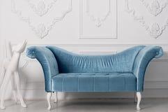Luxuriöses blaues Samtsofa und und weiße Skulptur eines Hundes Stockfotos