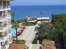Luxuriöses Hotel, Palmen, Swimmingpool und ein Schiff auf Meer Stockfotos