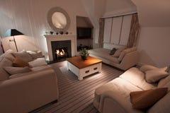 Luxuriöses modernes Wohnzimmer mit beleuchtetem Feuer Lizenzfreies Stockfoto