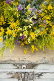 Luxuriant wildflowers bouquet on the old vintage pouf Royalty Free Stock Images