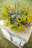 Luxuriant wildflowers bouquet on the old vintage pouf. Outdoor Royalty Free Stock Photography