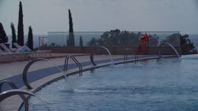 Luxurios resort swimming pool with metal waterfalls. On sunny summer hot day, ocean on background stock video