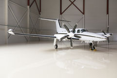Luxurious aircraft in a big hangar. Luxurious aircraft stored in a spacious hangar royalty free stock photography