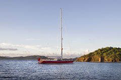 Luxurious anchored sailboat. Large luxurious red sailboat anchored in the virgin islands Royalty Free Stock Photo