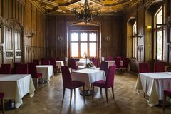 Classic gothic hall in restaurant in german castle or palace. Luxurious antique hall in restaurant with wooden walls, gothic windows with daylight and medieval stock photo