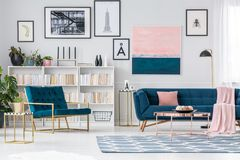 Luxurious apartment with blue armchair. Luxurious apartment interior with blue armchair, sofa and carpet with bookshelf in the background stock photos