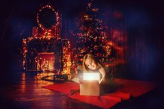 Luxurious apartment at christmas. Pretty nine year old girl opens a gift box and surprises. Luxurious apartments decorated for Christmas. Merry Christmas and stock images