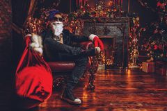 Luxurious apartment of santa. Ð¡heerful punk Santa with a bag of gifts in his hands in luxurious apartments decorated for Christmas. Bad Santa concept royalty free stock photos