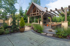 Luxurious Backyard. An upscale backyard terrace featuring perennials and with a custom designed shelter and fireplace Stock Images