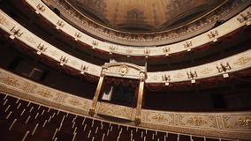 Luxurious balcony in concert hall, empty chairs rows, red draipings. Golden decorations, beautiful mural stock video