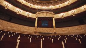 Luxurious balcony in concert hall, vacant chairs rows, red draipings. Golden decorations, beautiful mural stock video