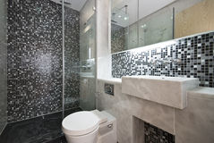 Luxurious bathroom in black and white. Modern bathroom in black and white with mosaic tiled walls and white ceramic wash basin and toilet Stock Images