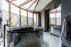 Luxurious bathroom with freestanding glossy bathtub. Luxurious bathroom interior with freestanding glossy bathtub, designed in dark tones Royalty Free Stock Photography