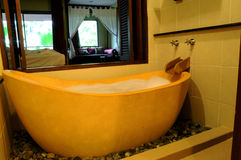 Luxurious bathtub. Closeup of luxurious modern, yellow bathtub in home Stock Image