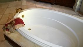 Luxurious Bathtub. With towels and gold fixtures in upscale home royalty free stock photo