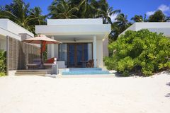 Luxurious beach villa on a snow-white beach. A luxurious dream hotel with a private pool. The luxurious Maldives. Dream vacation. The concept of a happy holiday Stock Photos