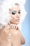 Luxurious beauty with crystal jewel. Luxurious beauty holding crystal jewel, wearing fancy makeup with strasses and white feather hat Royalty Free Stock Image