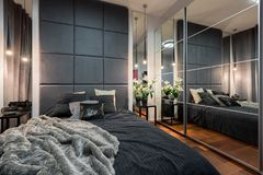 Luxurious bedroom with double bed. Luxurious big bedroom with comfortable double bed and mirrored wardrobe royalty free stock image