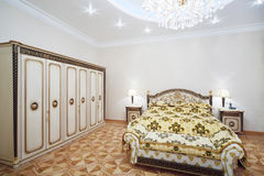 Luxurious bedroom with gilt double bed and wardrobe Royalty Free Stock Images