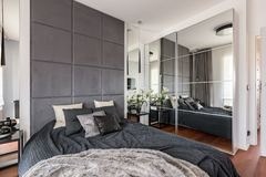 Luxurious bedroom with mirrored wardrobe. Double bed and upholstered wall royalty free stock photo