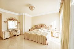 Luxurious bedroom in pastel colours in a neoclassical style, wit. H a large bed and a dressing table, with marble floors stock photos