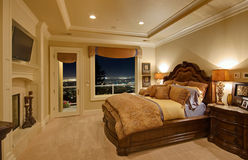 Luxurious Bedroom with a View. Bedroom in luxury home with view of city lights below stock photos