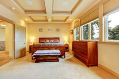 Luxurious big bedroom with wooden bed, vanity cabinet, trimmed c Royalty Free Stock Image