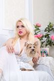 Luxurious blonde woman in a white dress with a dog  pekingese Royalty Free Stock Photo