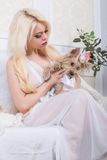 Luxurious blonde woman in a white dress with a dog  pekingese Royalty Free Stock Photography