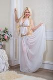 Luxurious blonde woman in a white dress Stock Image
