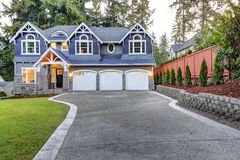 Luxurious blue home with three attached garage spaces Stock Photography