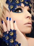 Luxurious blue makeup and manicures. Luxurious blue makeup and manicures on the girl with blond hair and decorative flowers on her head Royalty Free Stock Image