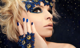 Luxurious blue manicure and makeup . Luxurious blue manicure and makeup on a girl with blond hair and decorative flowers on a dark background Stock Images