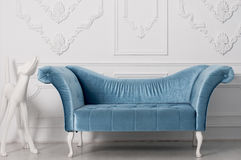 Luxurious blue velvet sofa  and  and white sculpture of a dog. Near the armrest behind a white wall Stock Photos