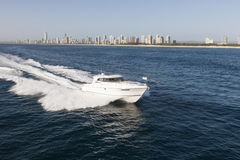 Luxurious boat sailing away from the city Royalty Free Stock Photo