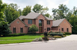 Luxurious Brick Home. Large, luxurious, brick suburban home with landscaping and driveway royalty free stock photo