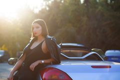 Luxurious brunette lady with red lips, posing in a convertible c. Luxurious brunette woman with red lips, posing in a convertible car with a sun light. Empty royalty free stock photo