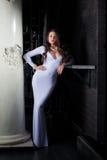 Luxurious brunette posing in elegant white dress Stock Image